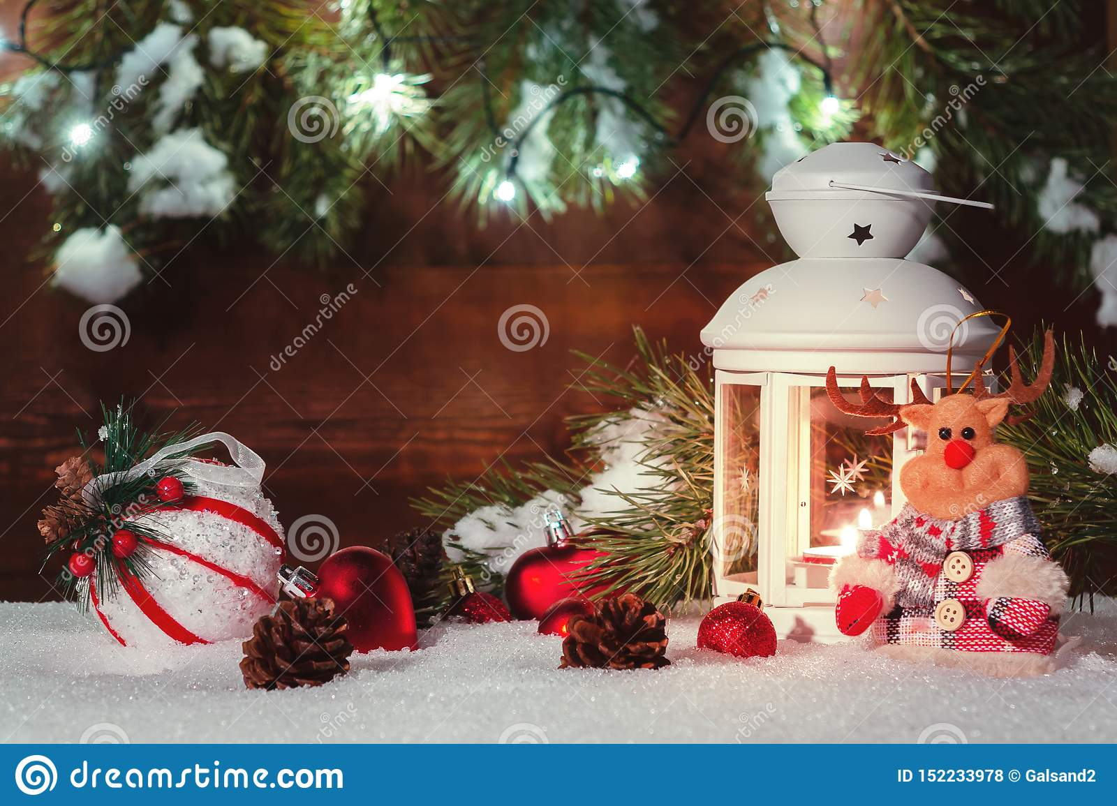 White Lantern With A Burning Candle Stands In The Snow Surrounded By Christmas Decorations On The Background Of A Wooden Stock Photo Image Of Ornamental Lantern 152233978