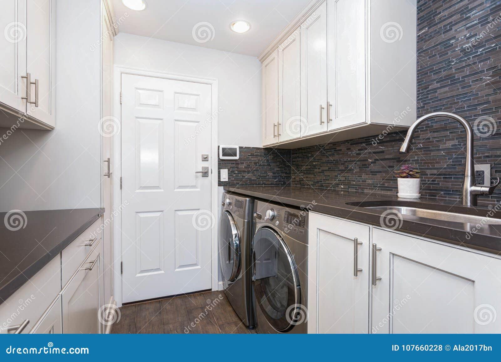 White Laundry Room Boasts White Shaker Cabinets Stock Photo Image Of Architecture Property 107660228