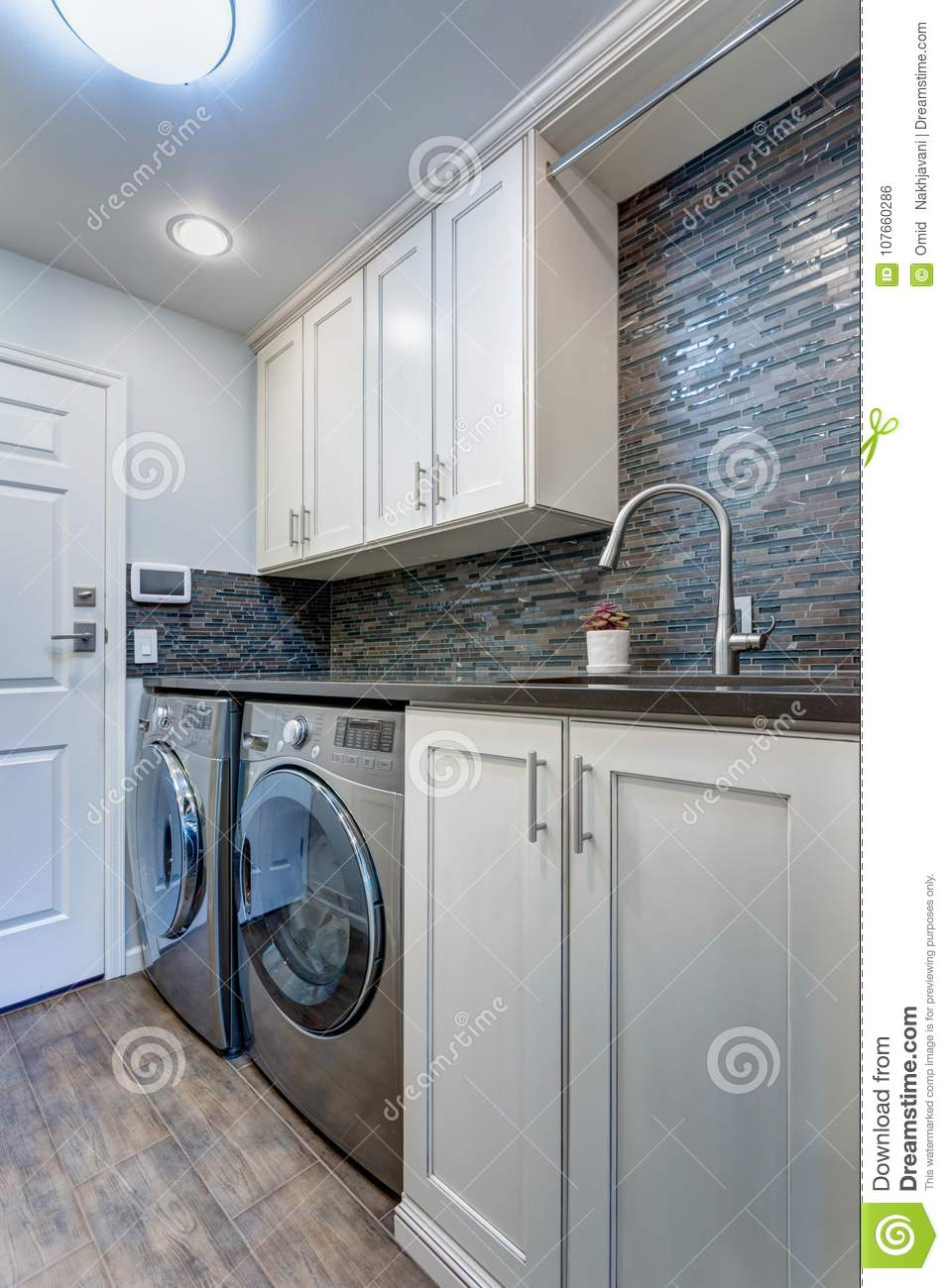Awesome White Laundry Room Boasts White Shaker Cabinets Stock Photo Interior Design Ideas Gentotryabchikinfo