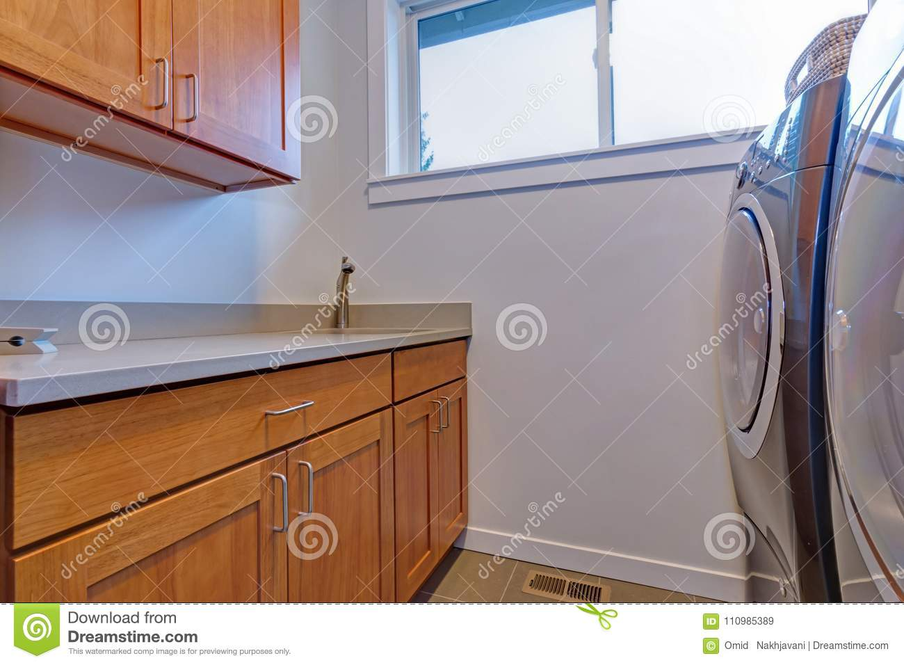 Interior of laundry room with wooden cabinets