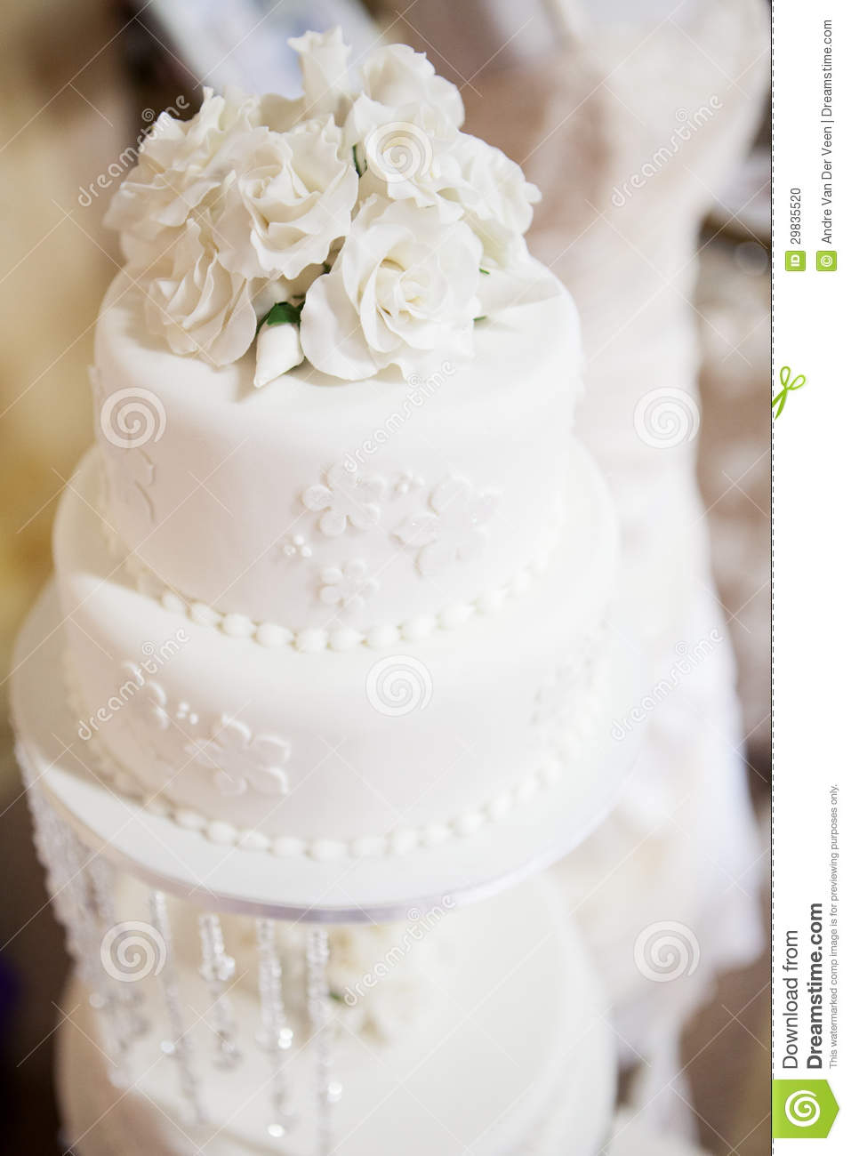 White Layered Wedding Cake With Roses On Top Stock Photo