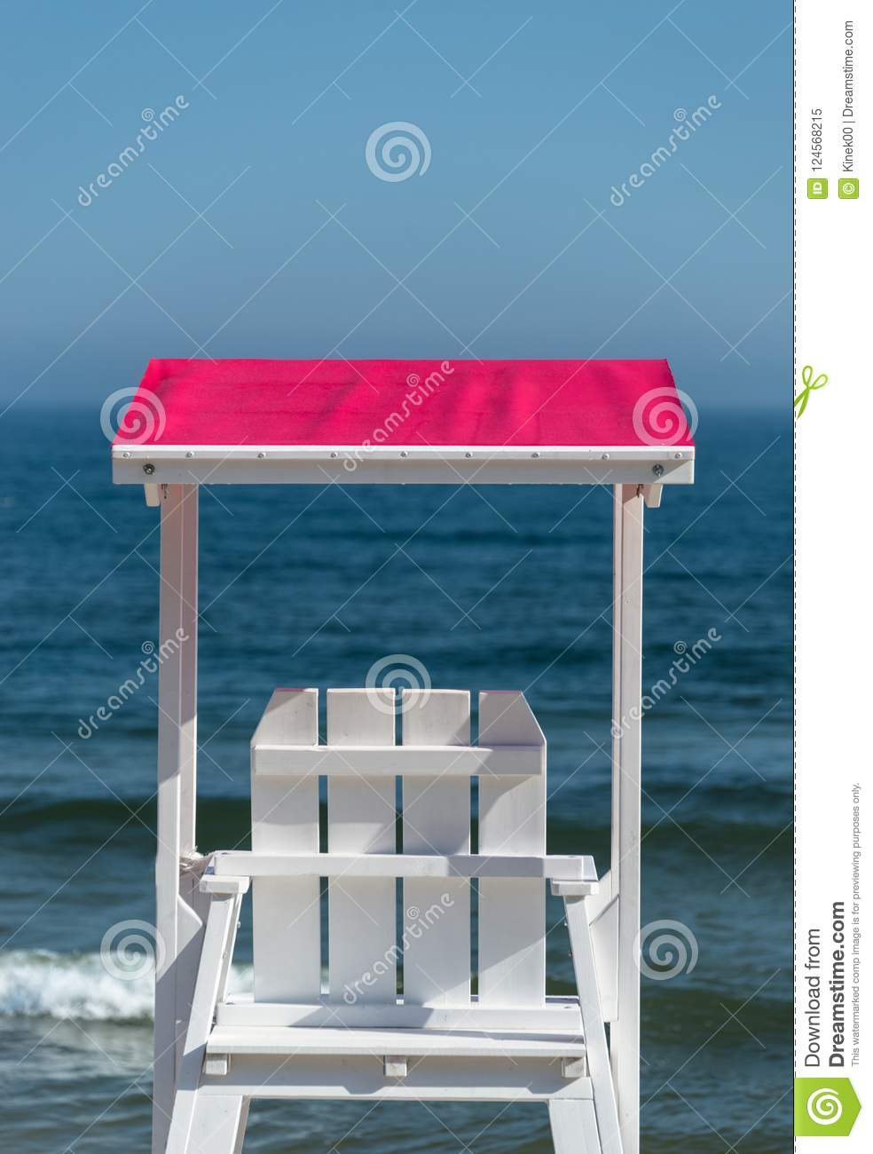 White lifeguard chair visible from the back with a pink visor against the background of a beautiful blue sea and sky on a summer s
