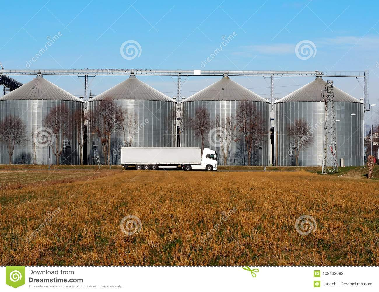 White Long Vehicle Trailer Truck In Front Of A Grain Storage Bins