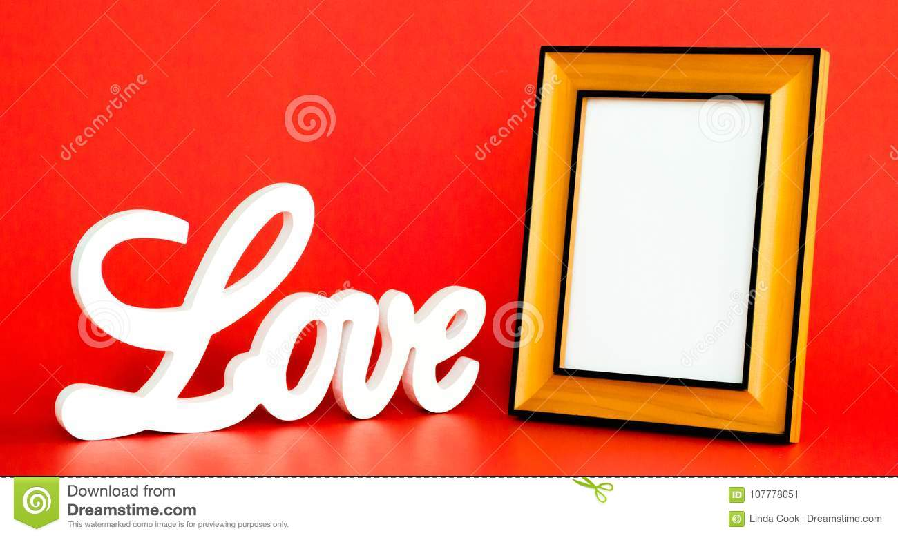 white love sign in cursive letters and empty picture frame to customize isolated on red background