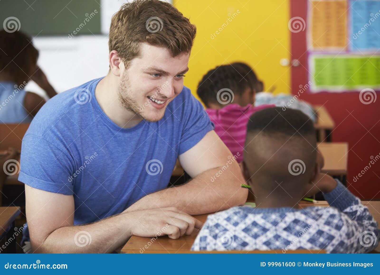 White male Volunteer teacher helping boy in elementary school class
