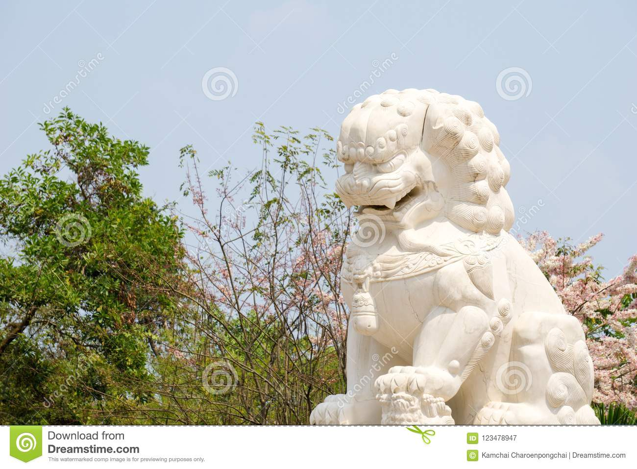 White marble Chinese guardian lion sculpture with tropical forrest