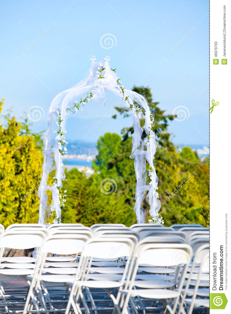 White Metal Folding Chairs Lined Up For Outdoor Wedding With Arb