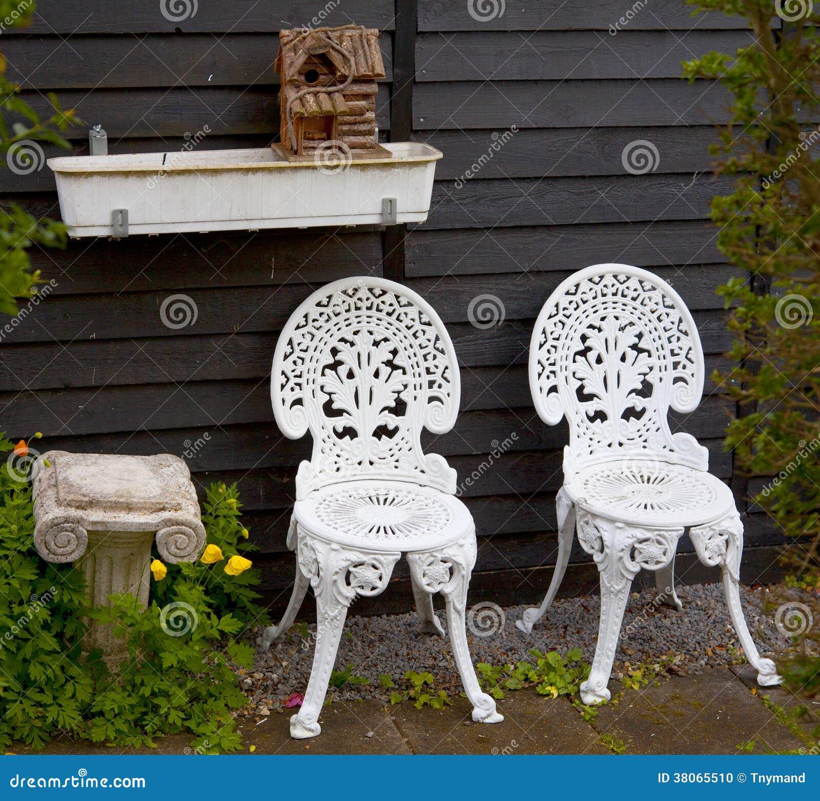 White metal garden chairs - White Metal Garden Chairs Next To Small Column And Birdhouse Stock Photo