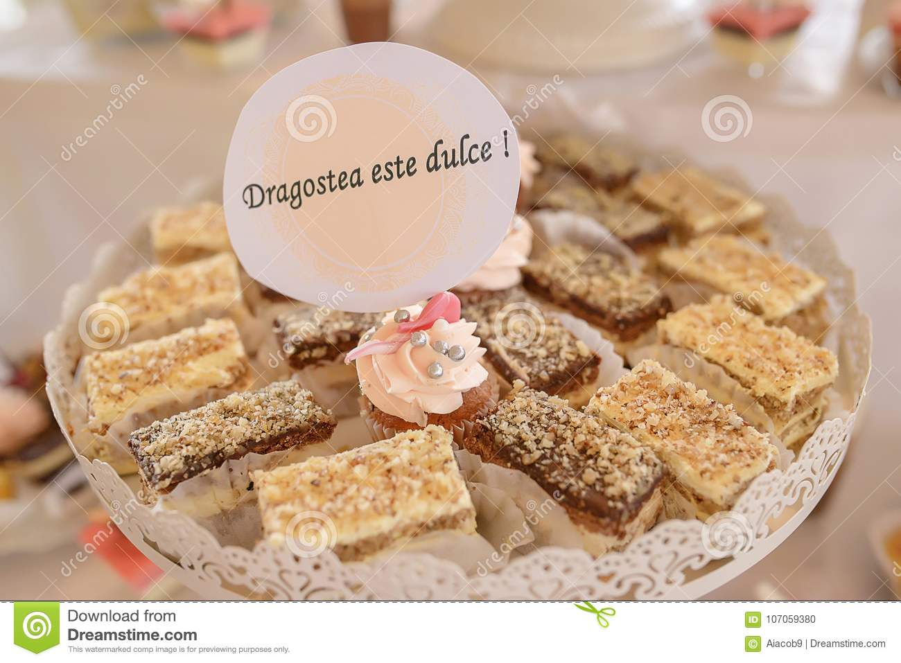 White metal tray with square cakes and one cupcake with the message in Romanian `Dragostea e dulce`, translating `Love is sweet`