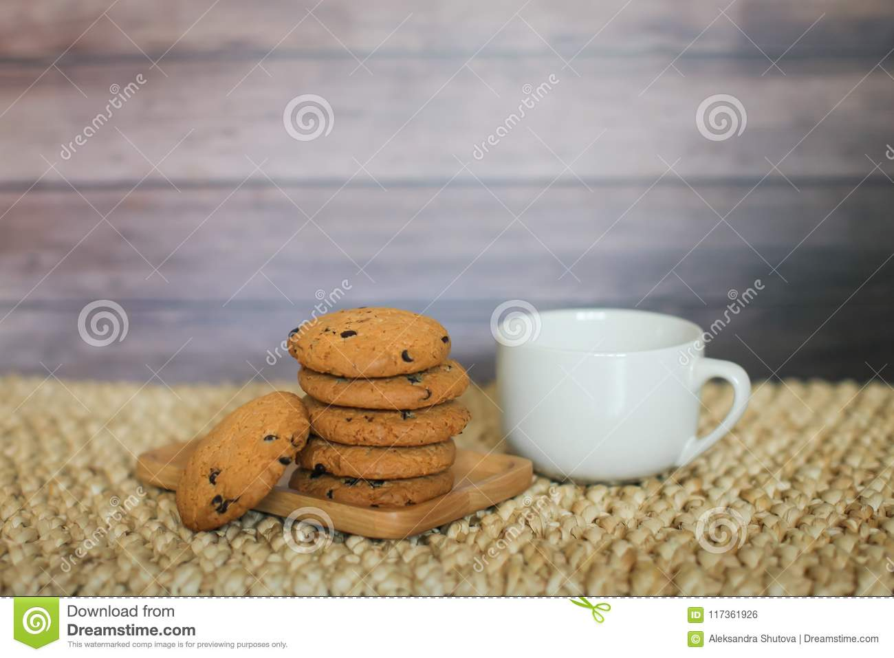 White mug and homemade oatmeal cookies folded in a pile on wooden plate and wooden background