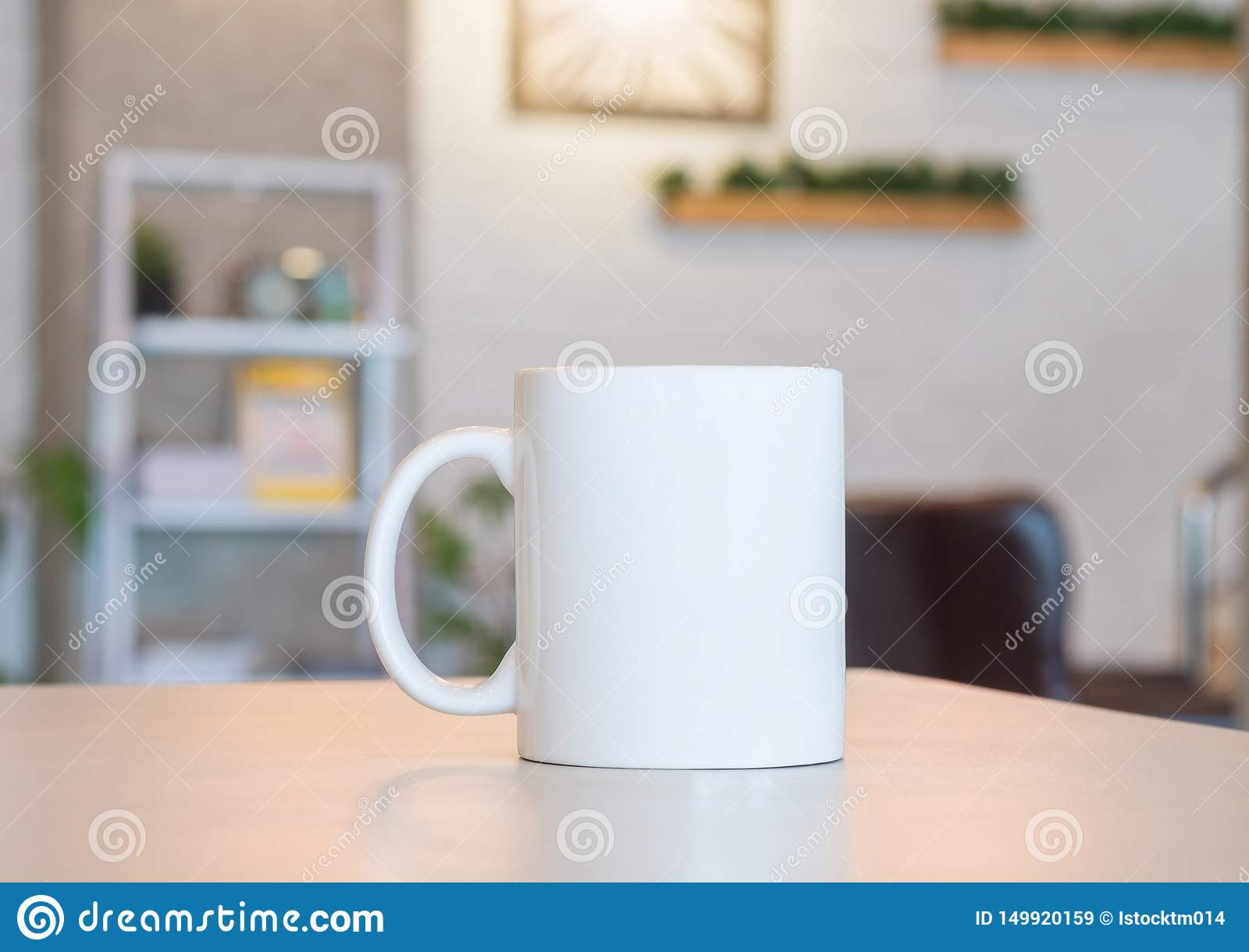 White mug on table and modern room background. Blank drink cup for your design. Can put text, image, and logo