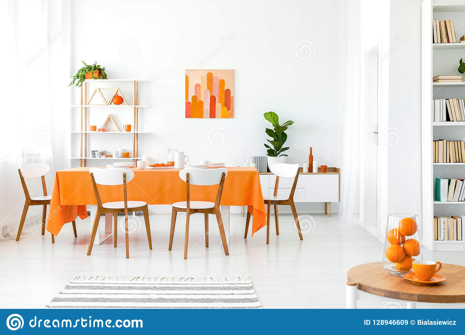 White and orange dining room with painting on the wall, bookshelf in the corner and green plant