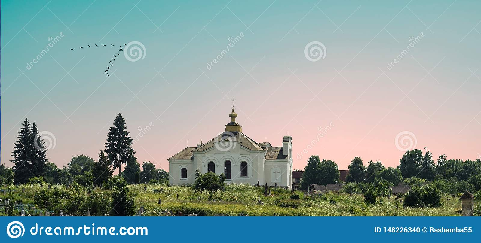 White orthodox church among the trees on the background of beautiful pink and blue sky