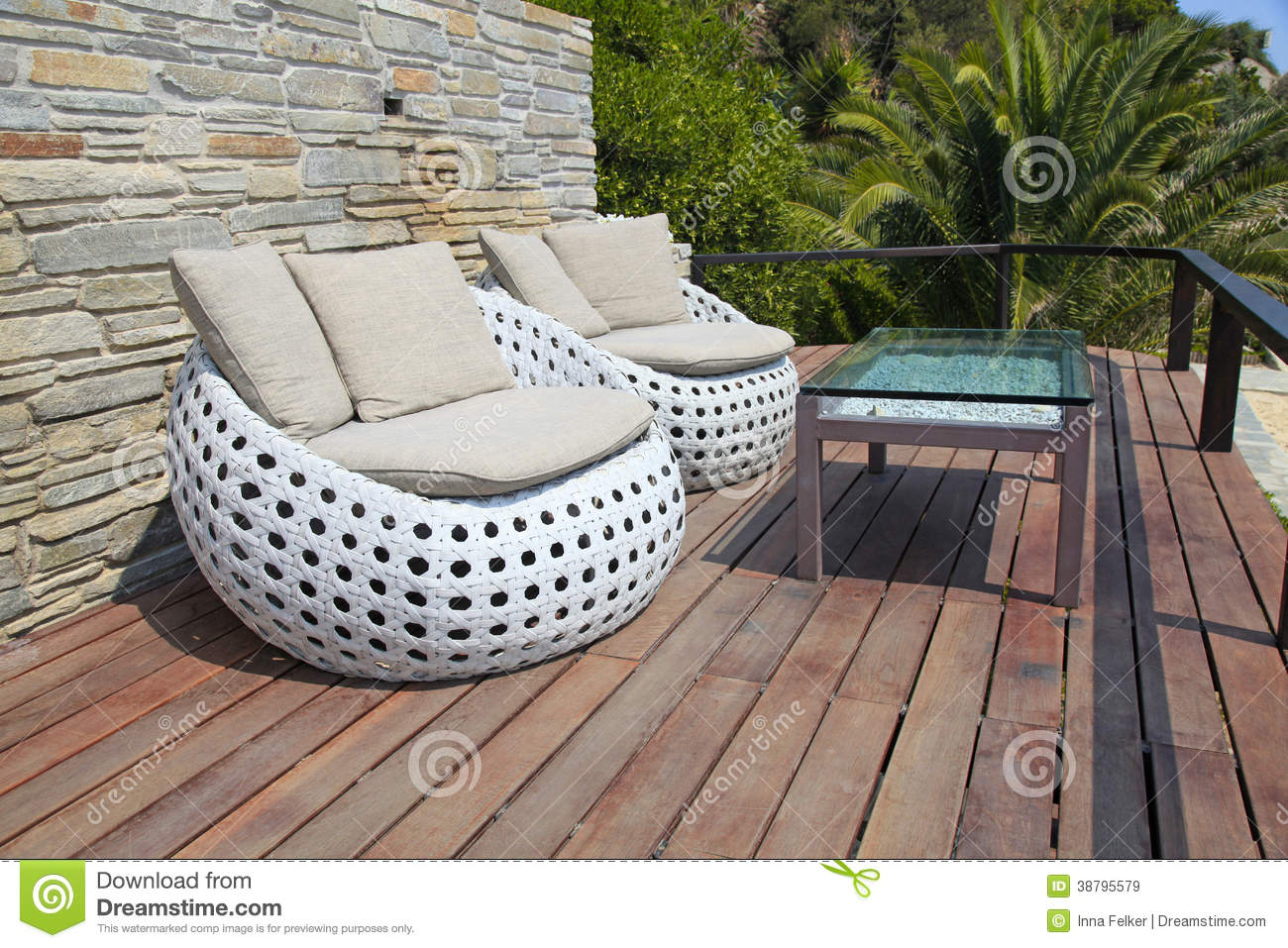 White outdoor furniture round rattan armchairs and glass table on wood ...