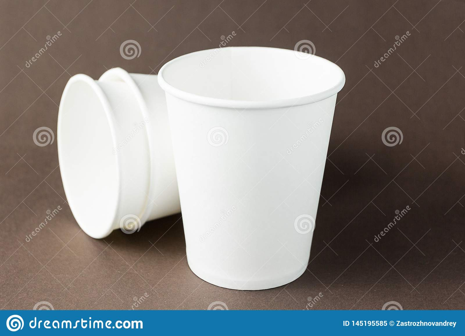 White paper cups mockup on brown background, space for text or label