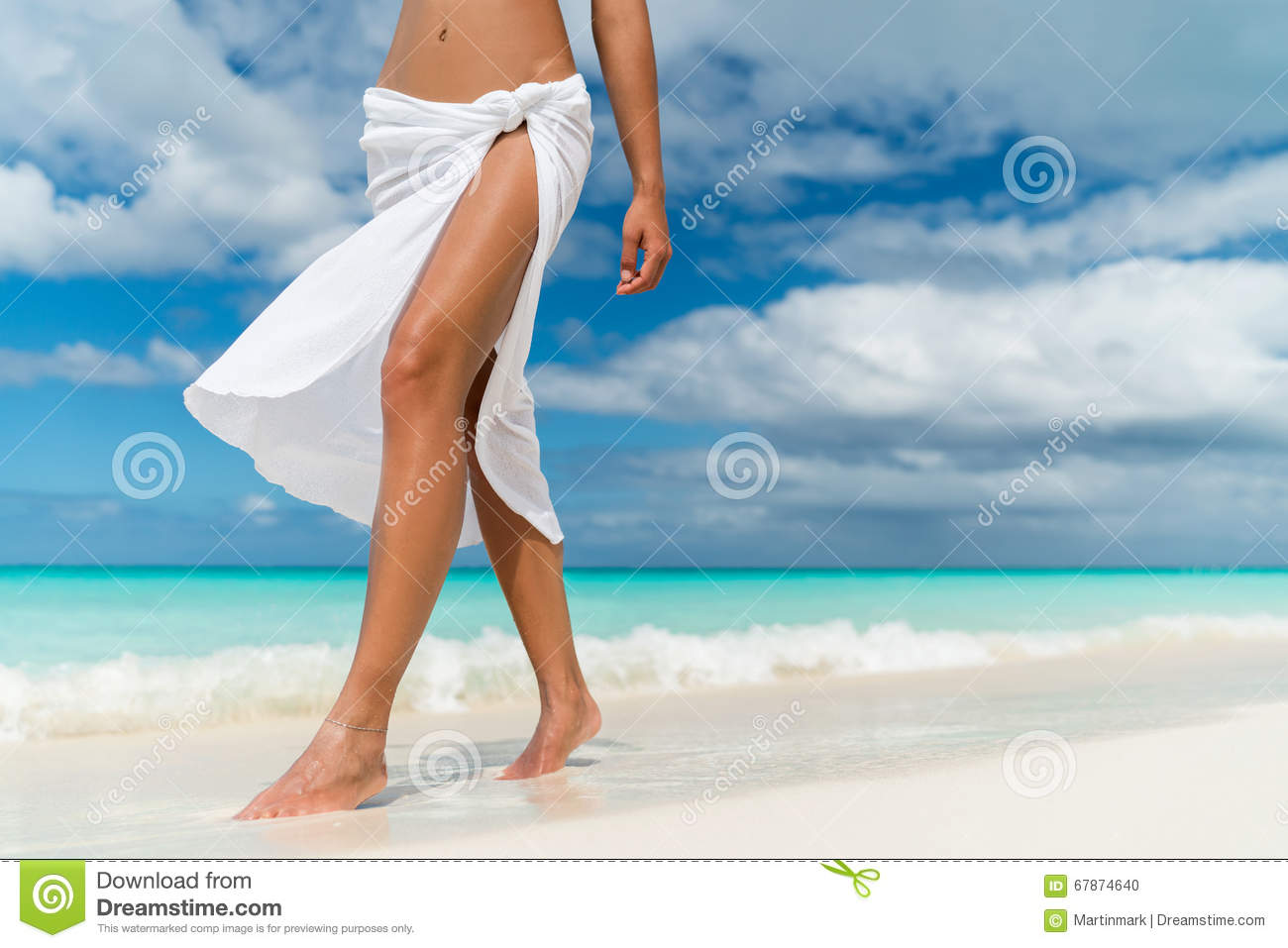 White pareo woman legs walking on tropical beach vacation