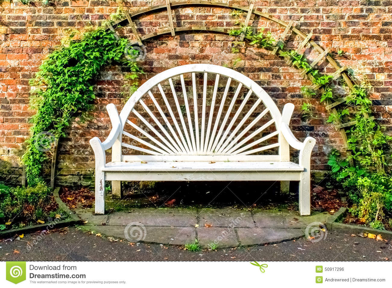 White Park Bench Seat Against Old Brick Wall Stock Photo
