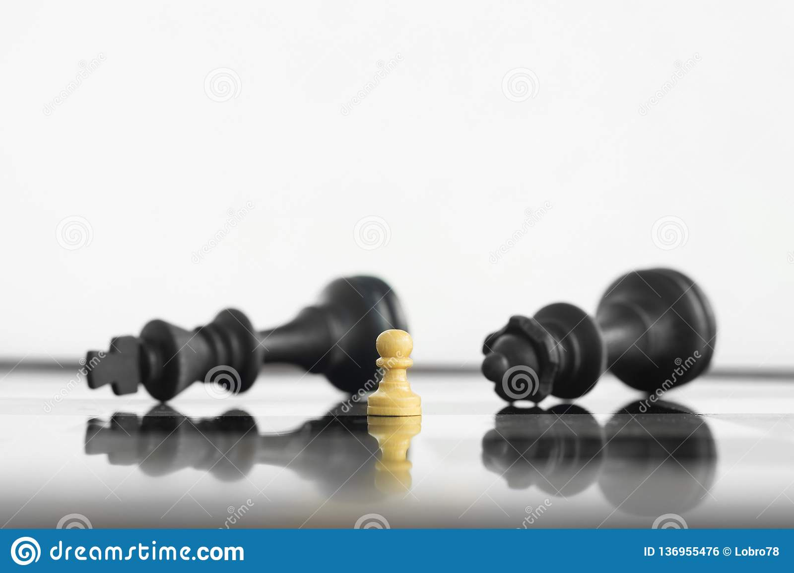 White peon standing victorious in front of a defeated King and Queen black chess army after confrontation