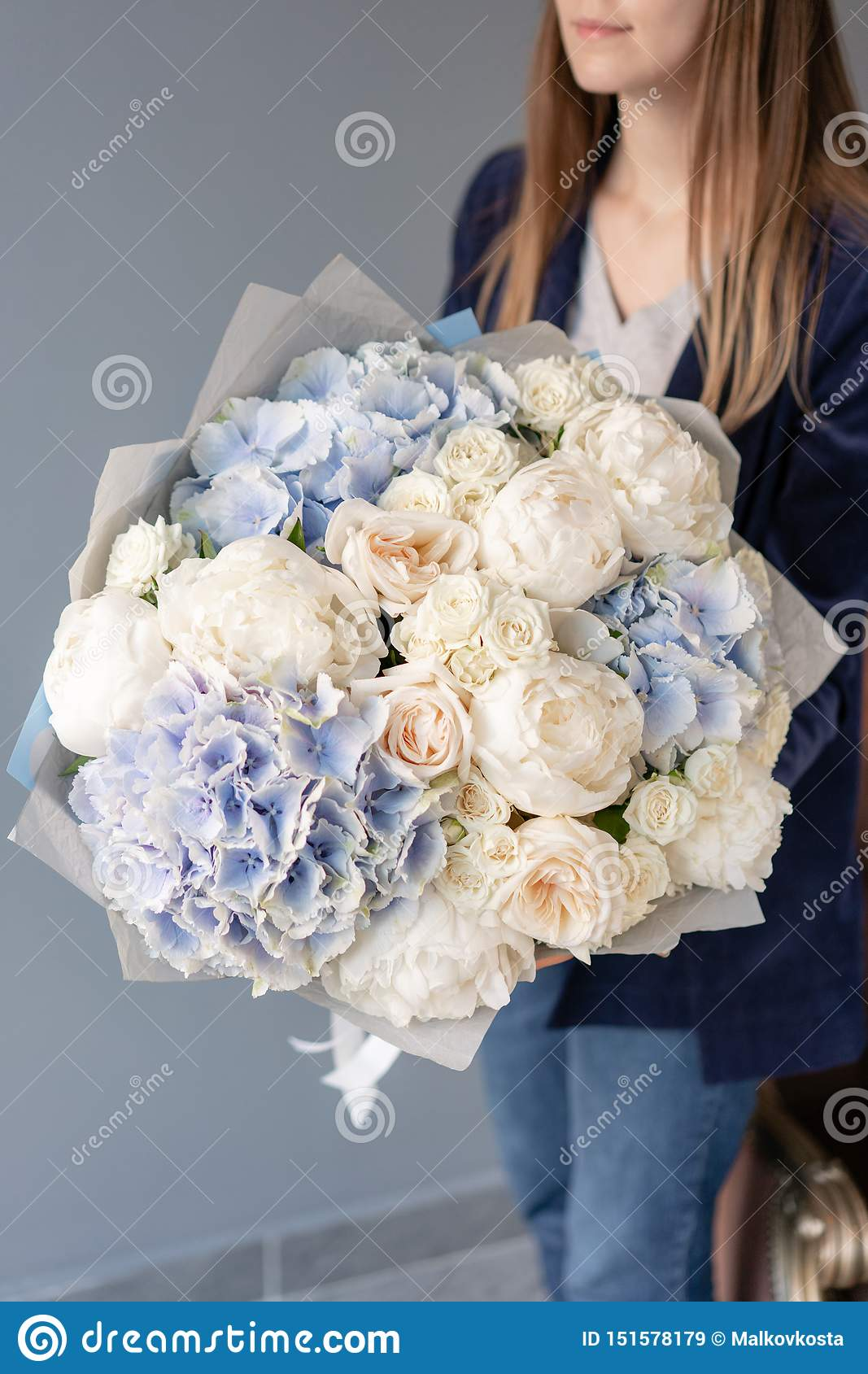 White peonies and blue hydrangea. Beautiful bouquet of mixed flowers in woman hand. Floral shop concept . Handsome fresh