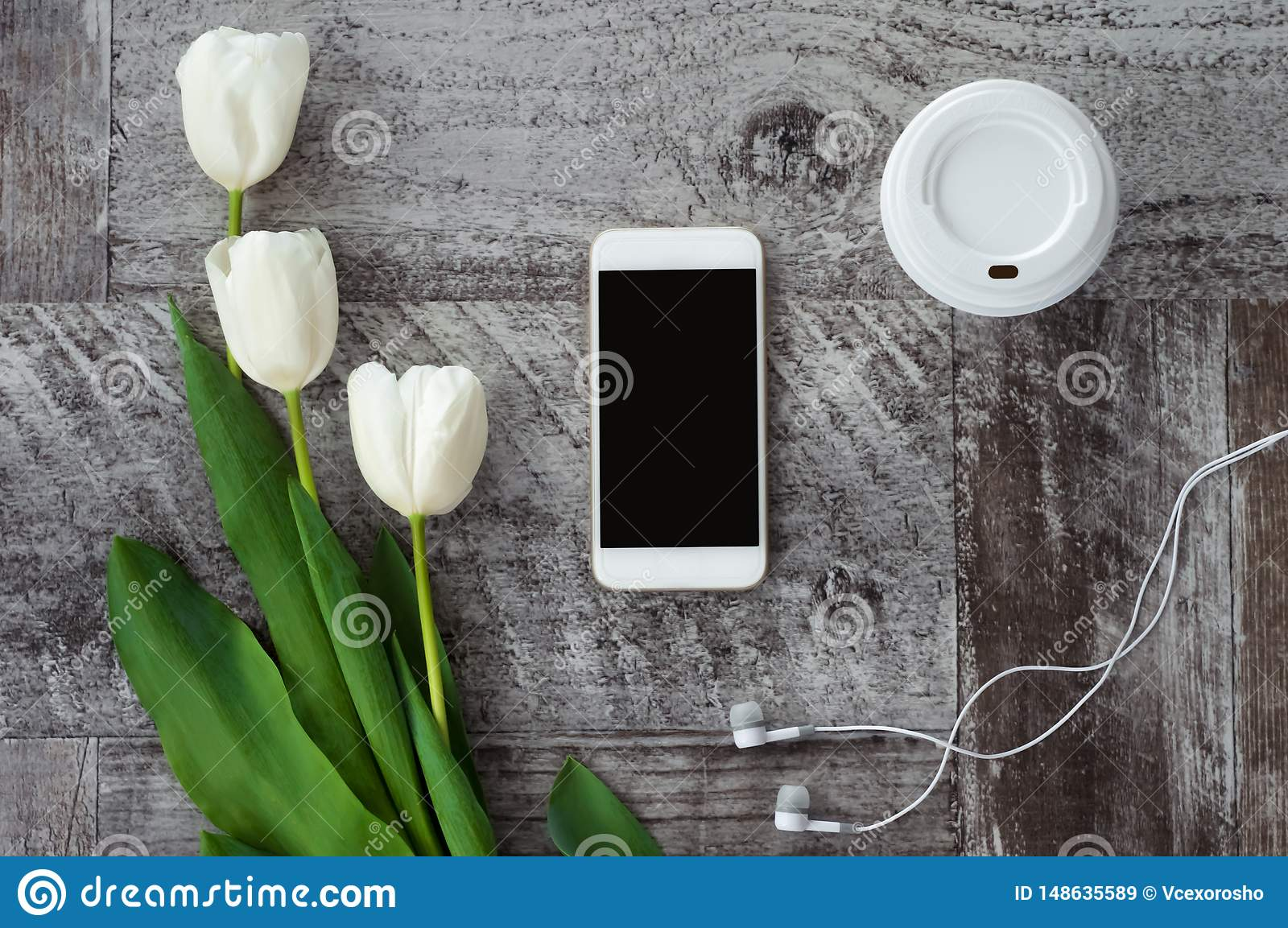 White phone with headphones, coffee and flowers are on the table. Work at home. Freelance