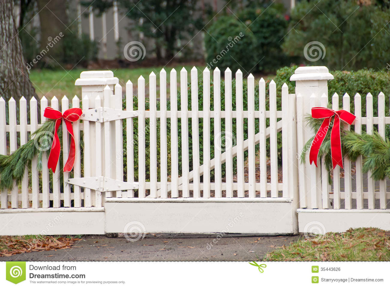White Picket Fence Garland And Red Bow Iv Stock Photo