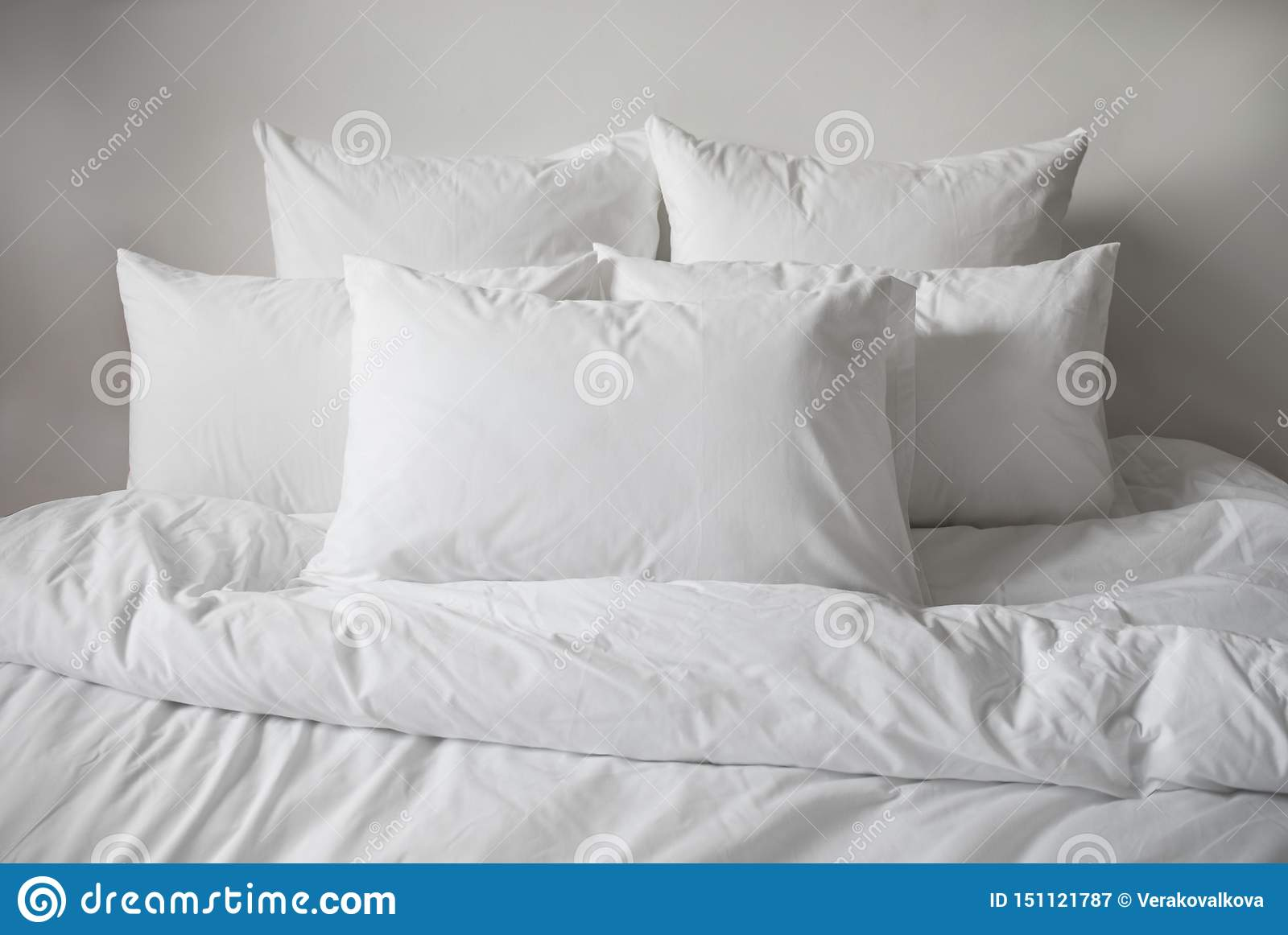 White pillows, duvet and duvetcase in a bed. Side view