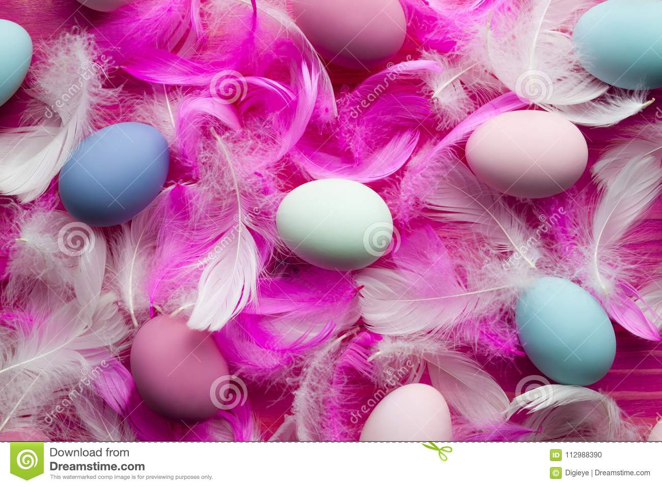 White and pink feathers and many colored Easter eggs