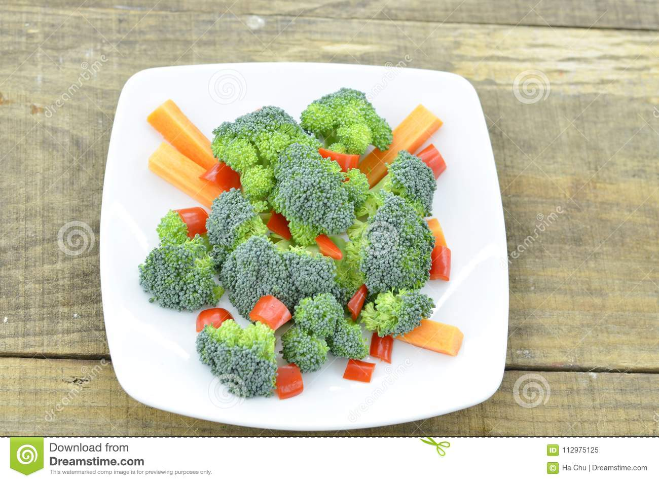 White plate with fresh vegetables on wooden background