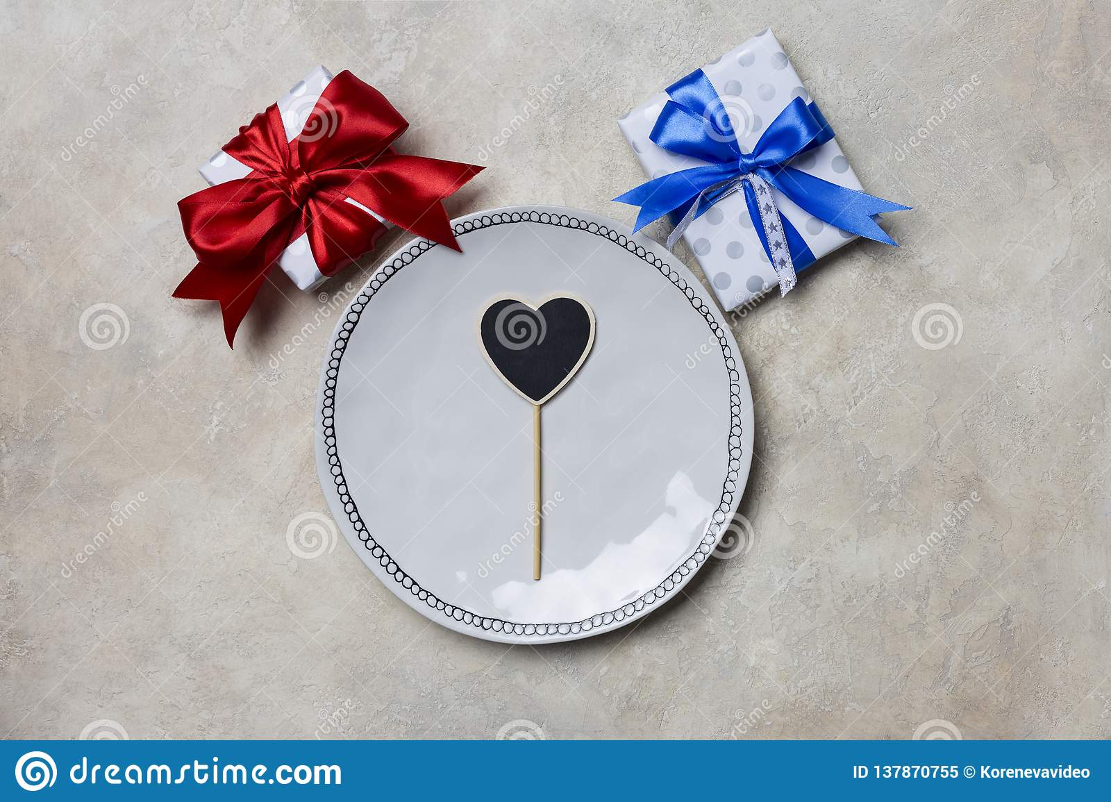 White plate with gift boxes with red and blue ribbons at white background