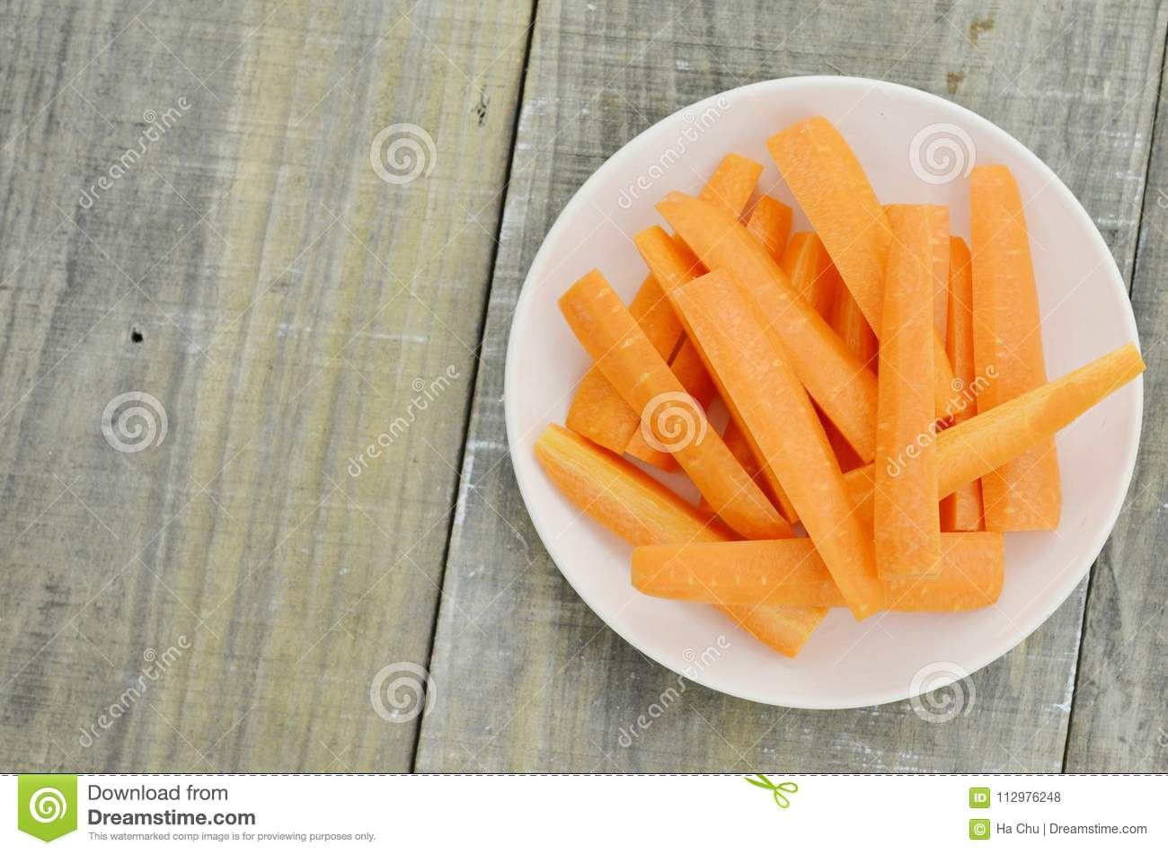 White plate with tasty carrots sticks on wooden table