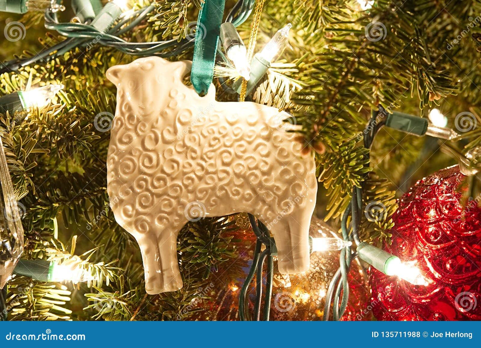 A white porcelain sheep folk art ornament on a Christmas tree.