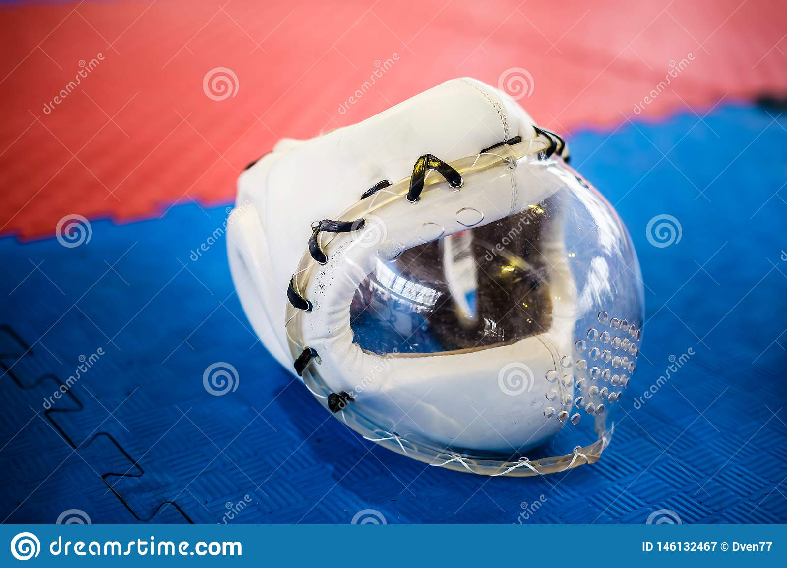White protective helmets with clear plactic mask for martial arts on the red blue floor