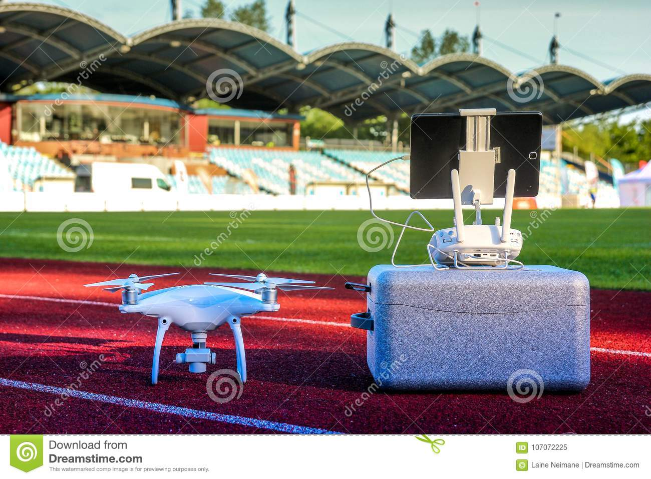 White quadcopter with four motors and propellers standing in large stadium
