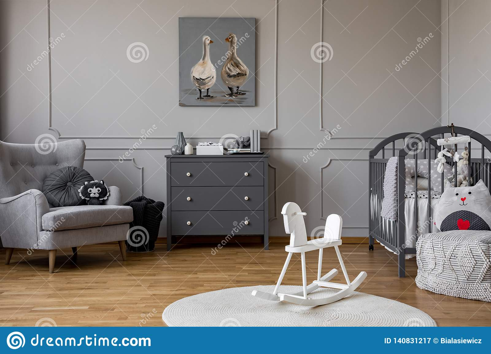 White rocking horse on rug in grey kid`s bedroom interior with poster above cabinet. Real photo