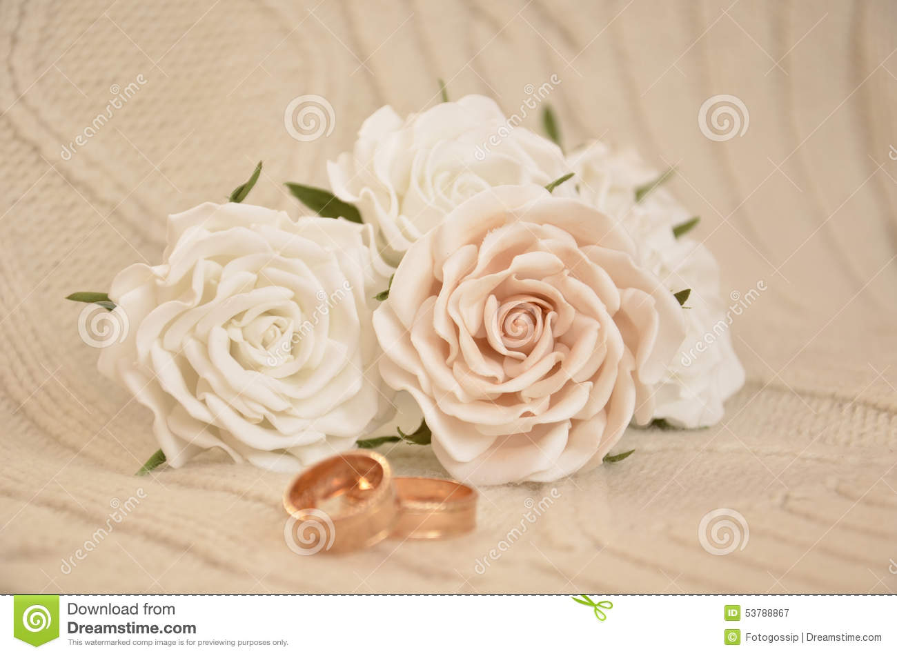 Wedding rings and white roses