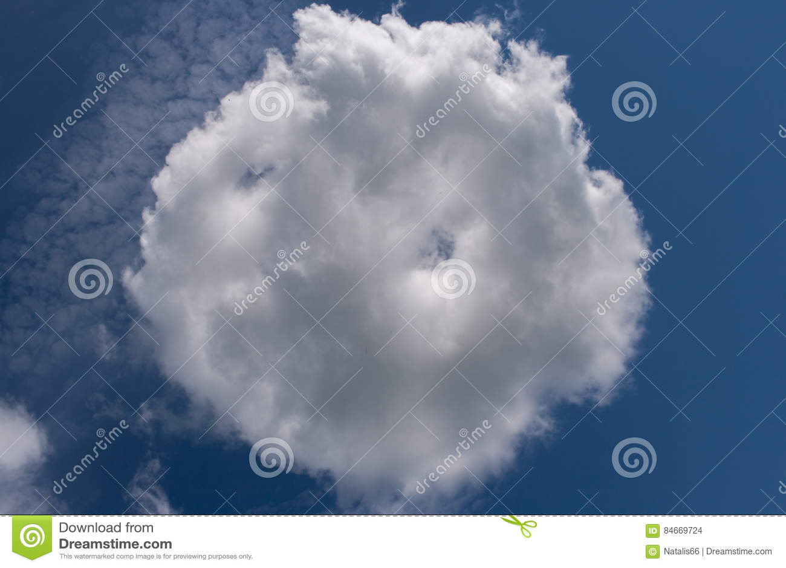 White round cloud, shaped like bun, on blue sky.