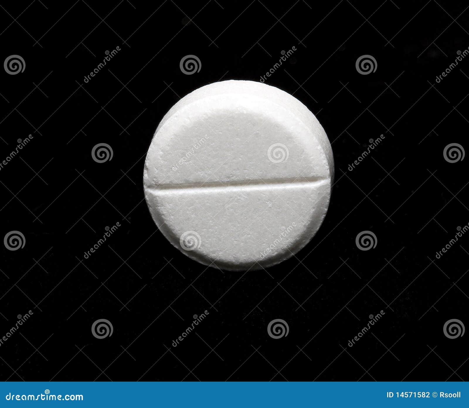 White round tablet of aspirin on a dark (black) background.