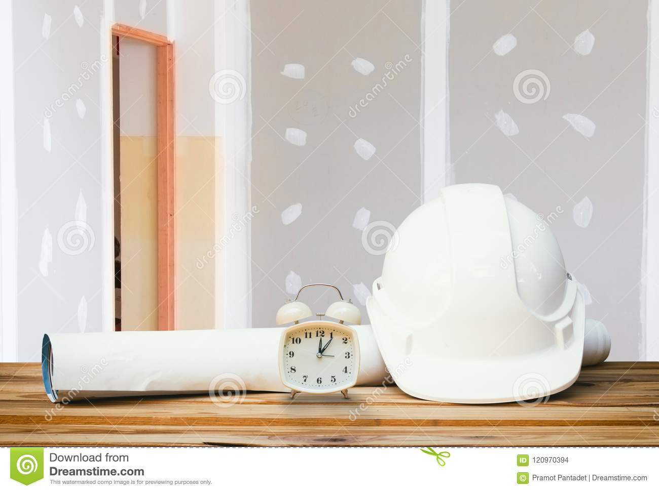 White safety helmet plastic, paper roll plan blueprint alarm clock time a rest at noon on wood floor table and gypsum board wall