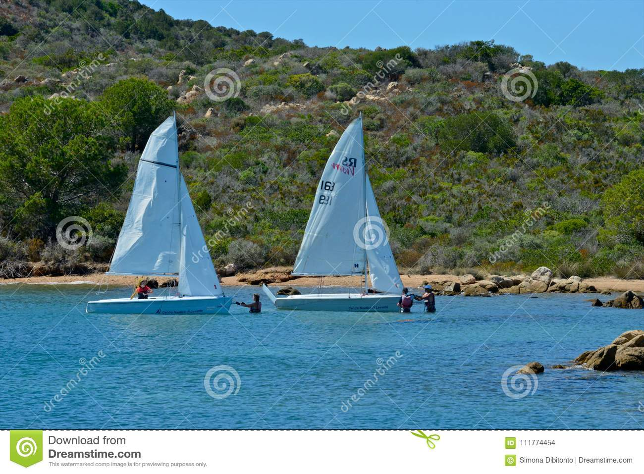 White sail boats with people learning to sail in the blue sea surrounded by nature