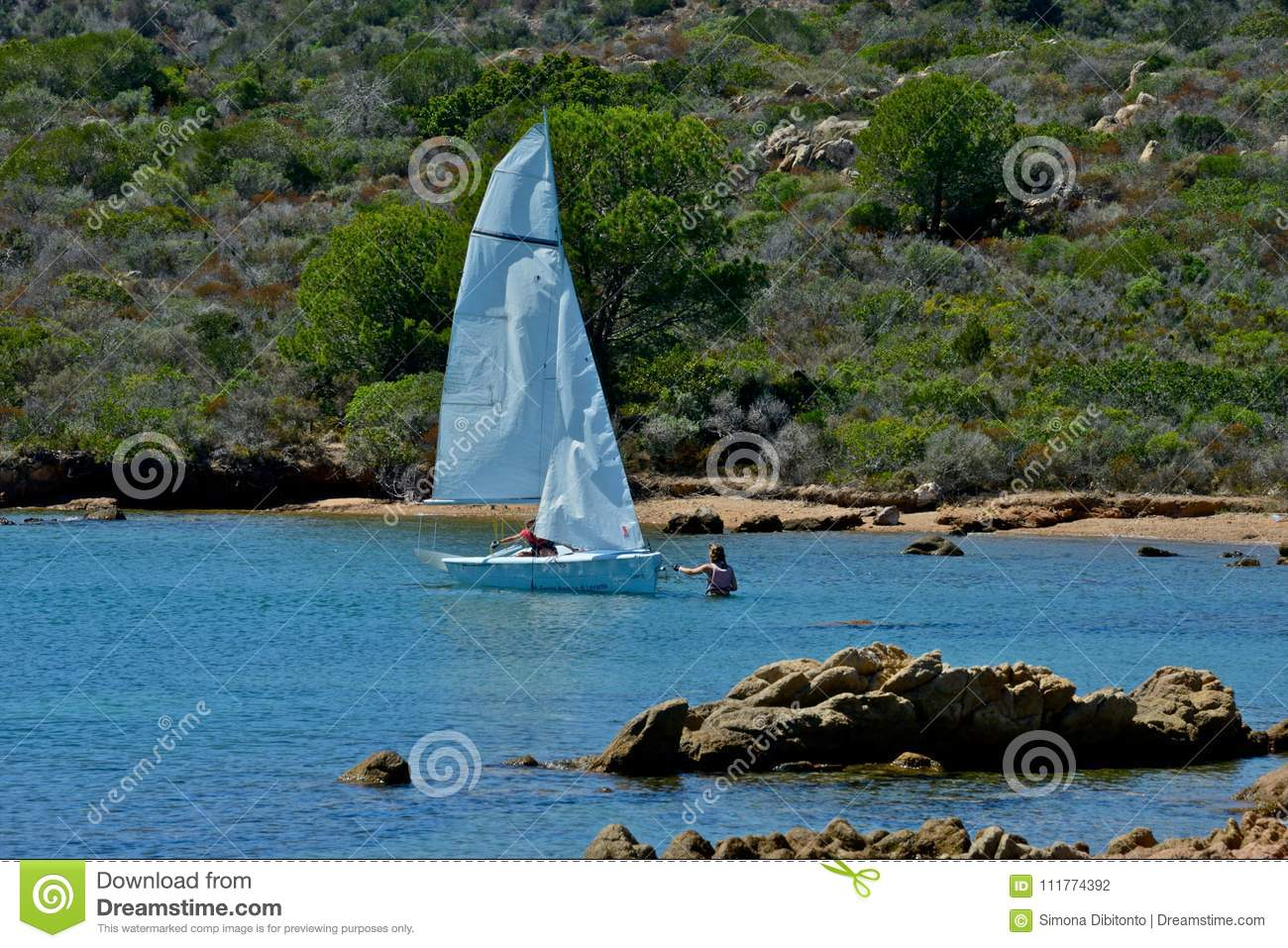 White sail boats with two people learning to sail in the blue sea surrounded by nature