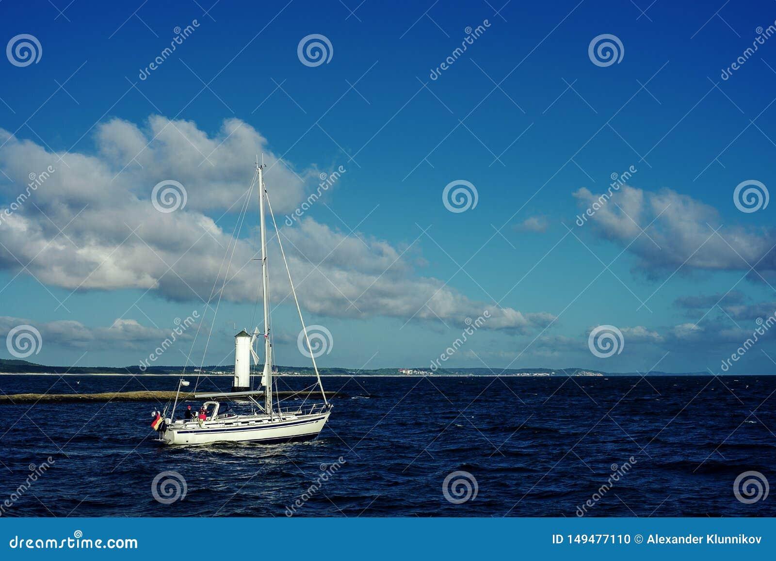 White sailing boat under way using engine on the background land.