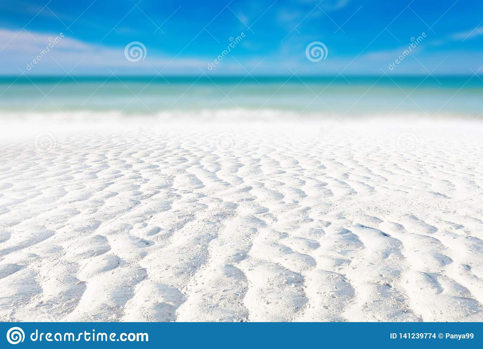 White sand curve or tropical sandy beach with blurry blue ocean and blue sky background image for nature background or summer