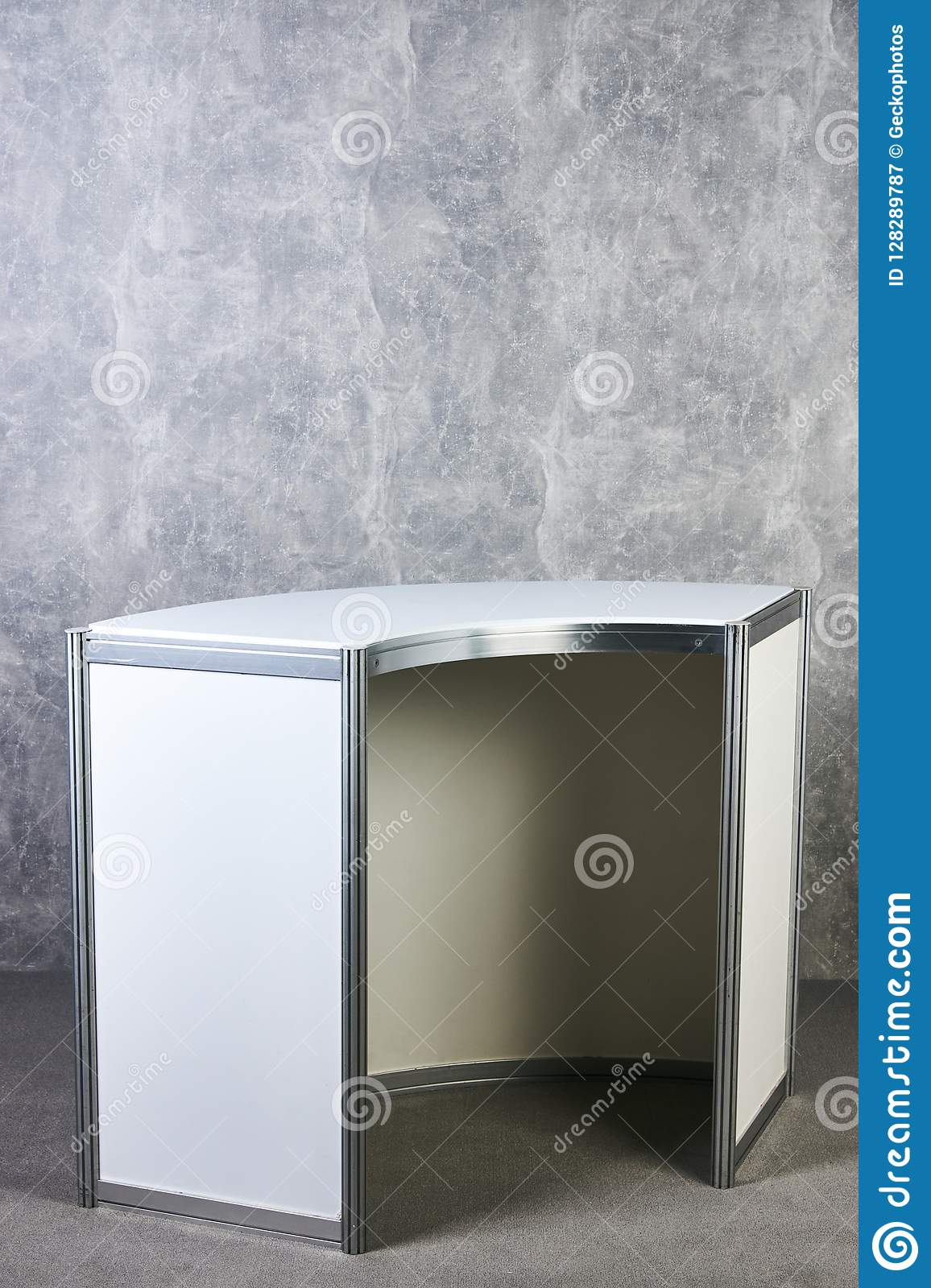 White showcase stand against gray textured wall background international exhibition furniture elements in large warehouse interior