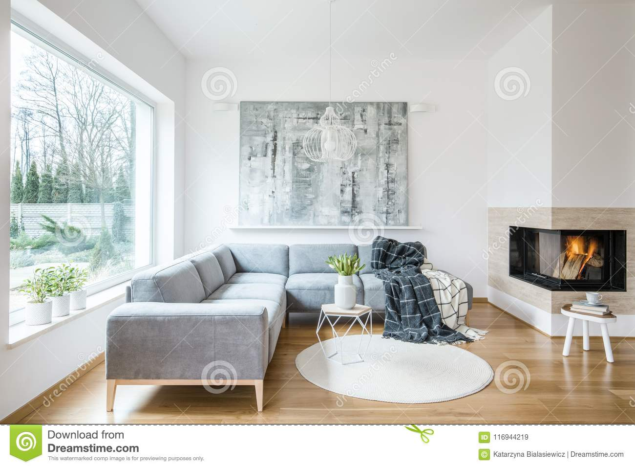 White sitting room interior with corner grey sofa, tulips in vase placed on end table, fireplace and modern art painting
