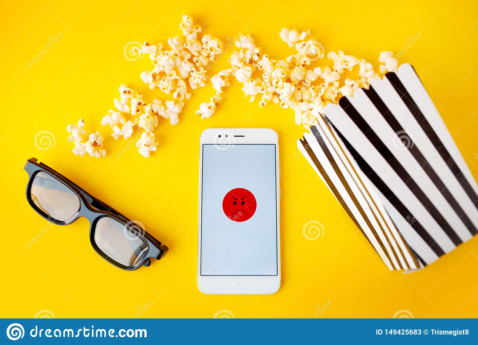 A white smartphone with smilies on the screen, 3d glasses, a black and white striped paper box and scattered popcorn
