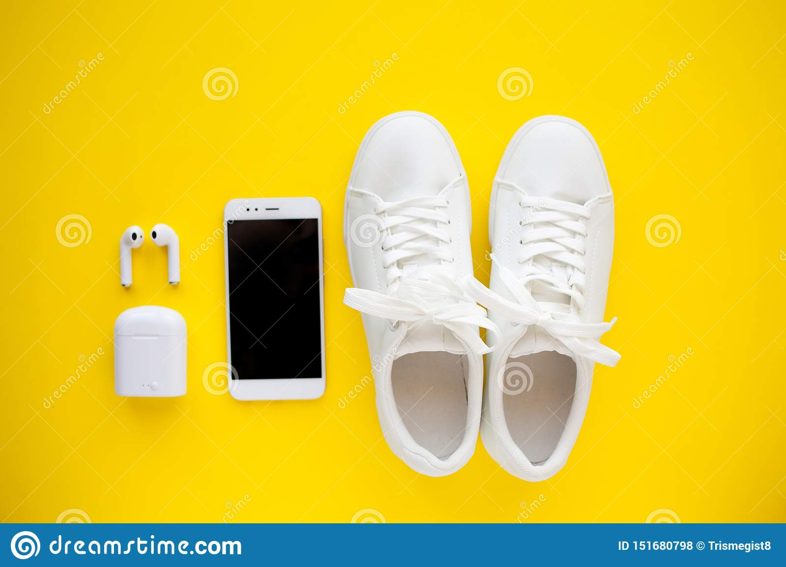 White sneackers, wireless headphones and smartphone are lying on a bright yellow background.