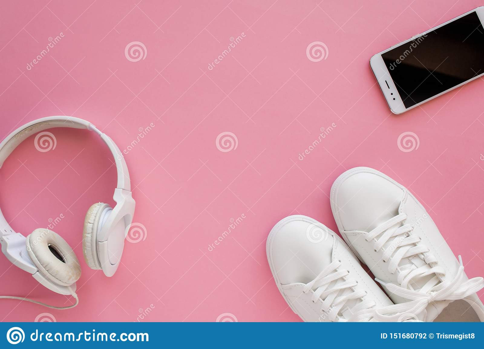 White sneakers, headphones, smartphone are lying on a bright pink background.