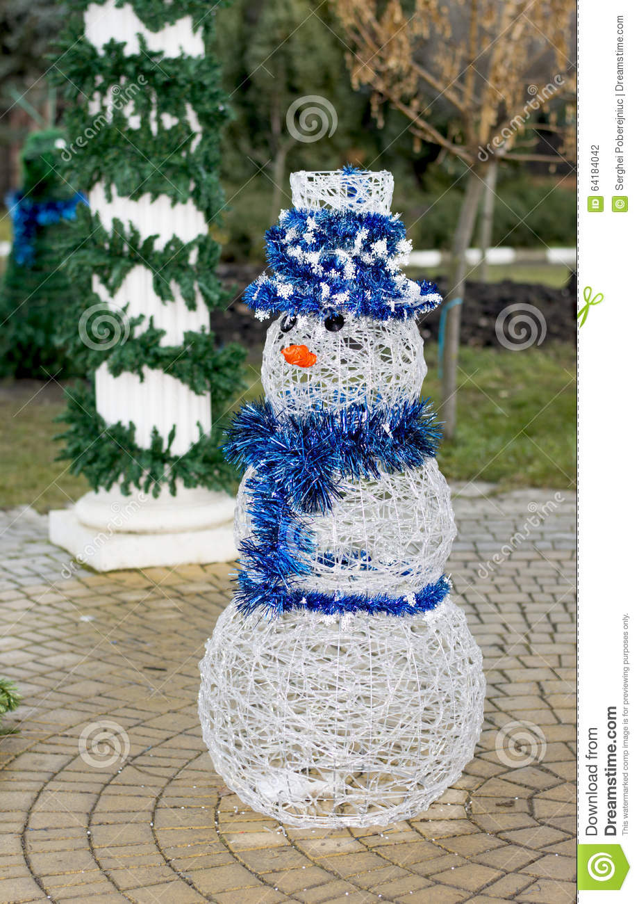 White snowman in a blue hat at the column decorated with a fir t stock
