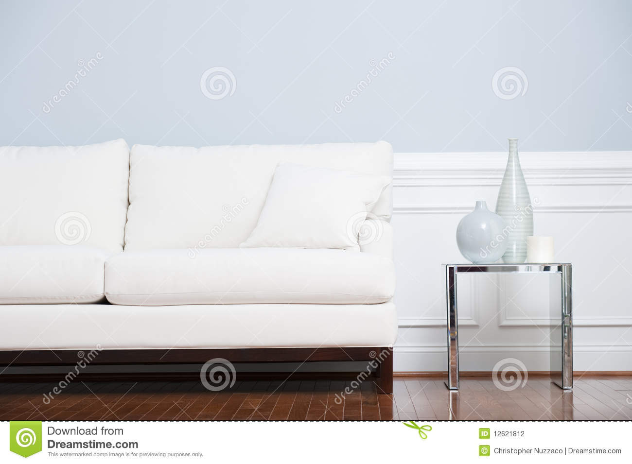 White sofa and glass end table against blue wall stock for Sofa wall table