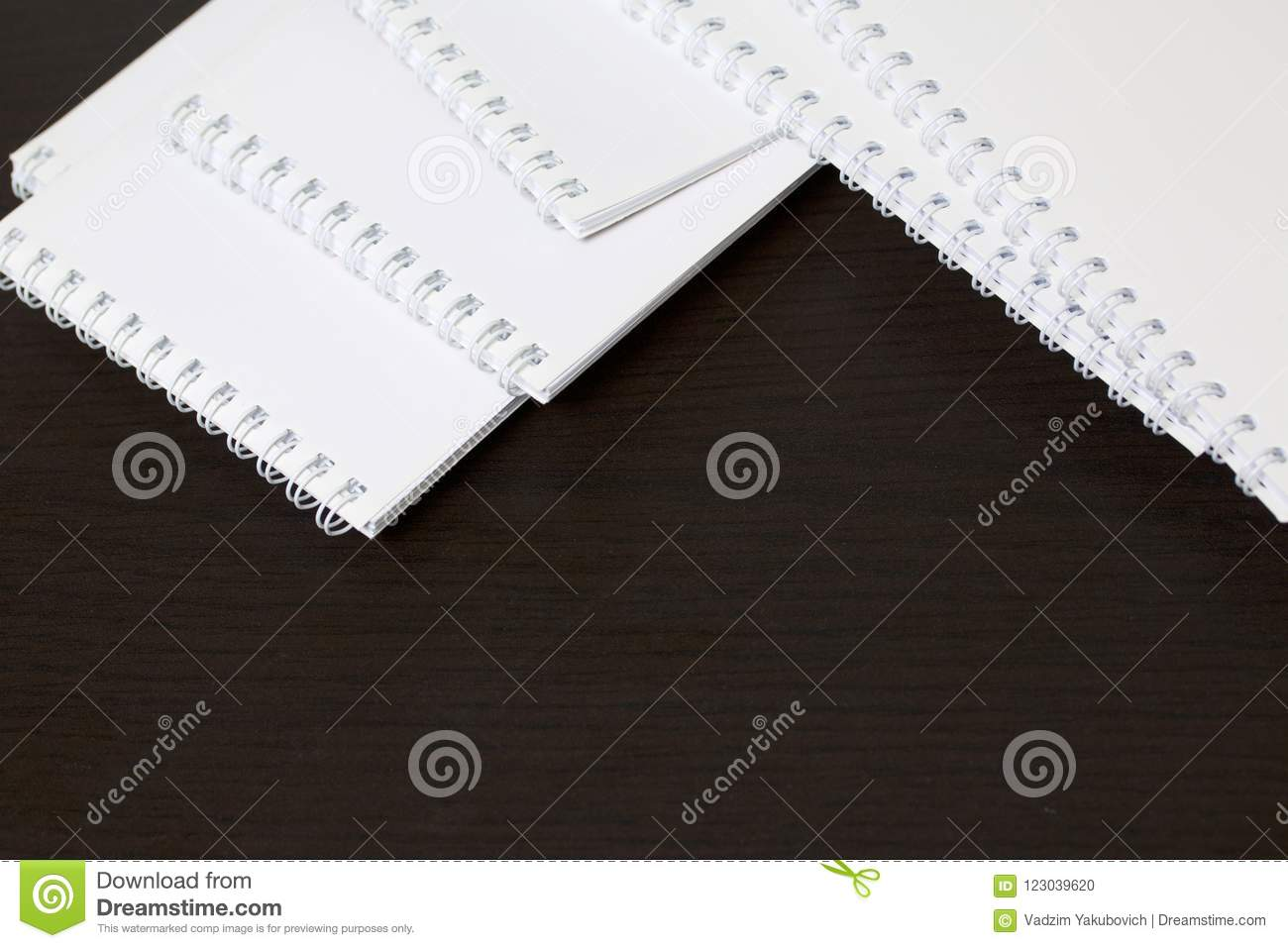 White spring notebooks for notes and sketches. Stationery for school and teaching. On a dark background.
